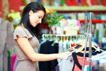 clearance sale: pretty elegant woman shopping in clothes store