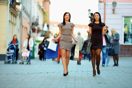 two elegant women walking the crowded city with shopping bags photo