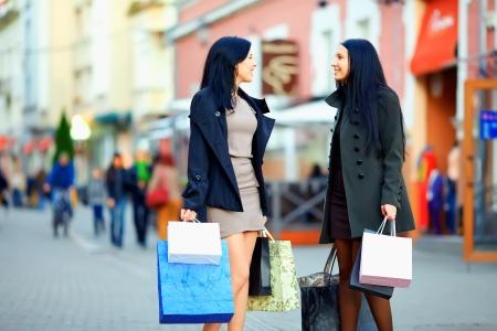 mooie elegante vrouwen lopen de drukke straat in de stad met boodschappentassen