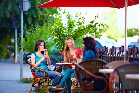 junge Freundinnen auf Café-Terrasse, Stadt im Freien sitzen