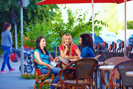 outside outdoor outdoors exterior: beautiful female friends sitting on cafe terrace Stock Photo
