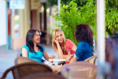 three persons: happy friends talking in summer cafe, urban outdoors
