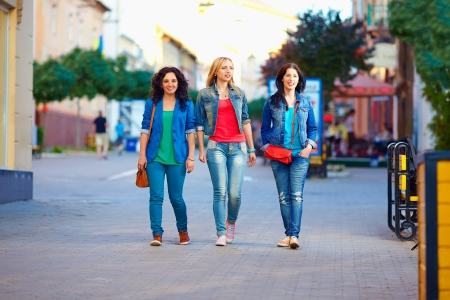three young girls walking the city street photo