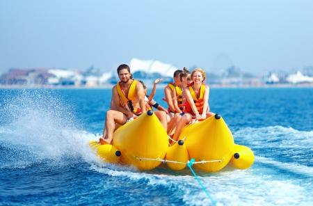 activity holiday: happy people having fun on banana boat