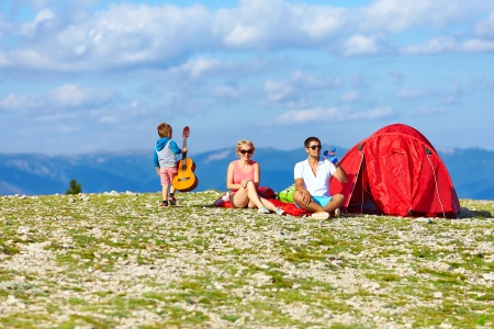 happy family camping in mountains photo