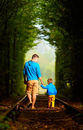 father and son together in railway green tunnel photo