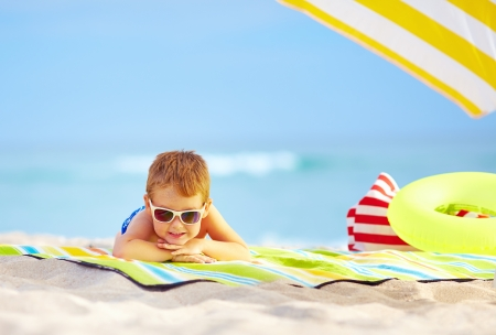 cute kid in sunglasses resting on colorful beach photo