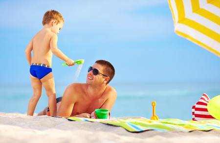 playful son strews sand on father, colorful beach photo