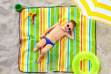 happy kid sunbathing on colorful beach photo