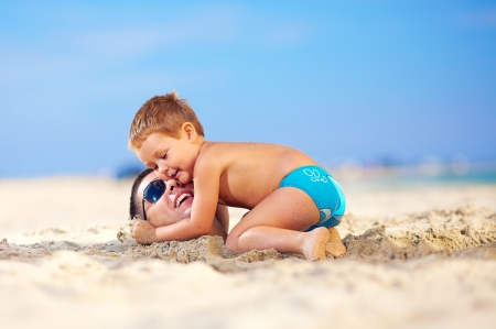 happy kid gently hugging fathers head in sand on the beach photo