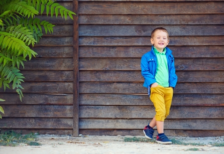 young boy smiling: portrait of cute fashionable boy in front of wooden wall