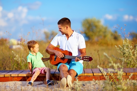 portrait of cute boy playing a guitar on summer field photo