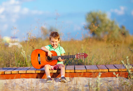 playing the guitar: portrait of cute boy playing a guitar on summer field