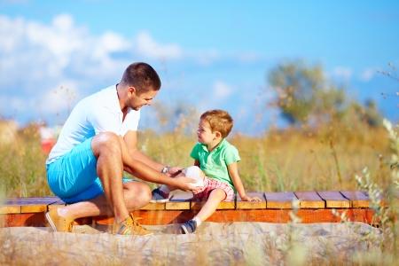 father bandaging injured leg of kid photo