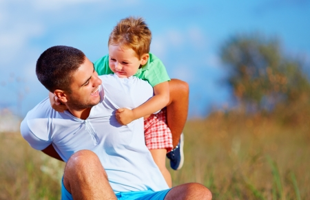 kinship: father and son having fun playing at summer field Stock Photo