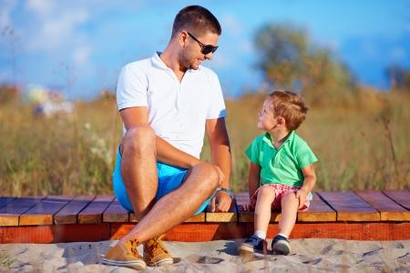 niños platicando: padre e hijo hablando, verano al aire libre Foto de archivo
