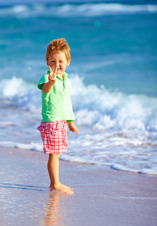 cute boy on beach, showing victory gesture photo