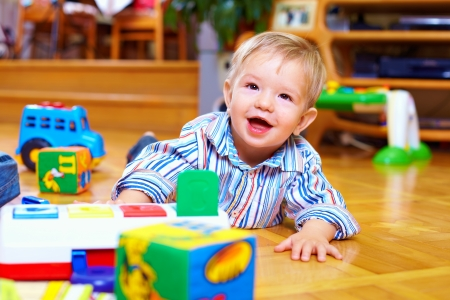 cute baby boy playing with toys in living room photo