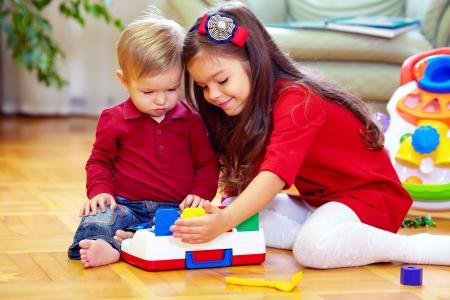 playing: hermosa ni�a jugando con el peque�o hermano en su casa