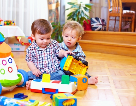 two cute baby toddlers playing in nursery room photo