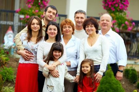 семья: большая счастливая семья портрет, дома двор Фото со стока