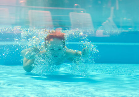 plunge: happy kid dives underwater in the pool