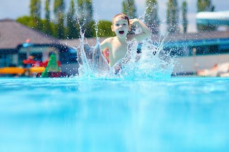 reir: niño feliz niño saltando en la piscina