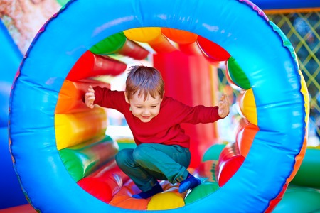 children at playground: ni�os felices jugando en la atracci�n inflable parque infantil