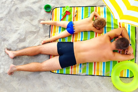 father and son sunbathing on colorful blanket