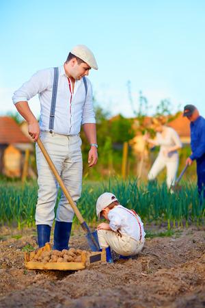 family planting potatoes in vegetable garden