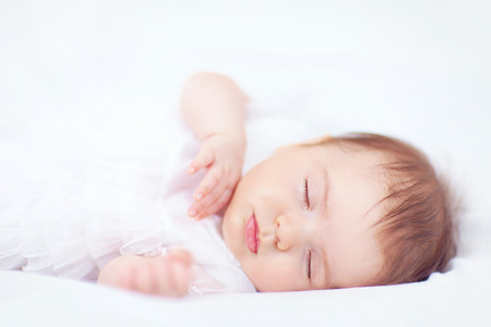 beautiful baby girl sleeping in white bed, two months old photo