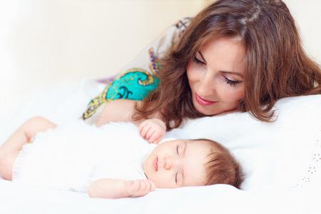beautiful mother watching newborn daughter sleeps Stock Photo