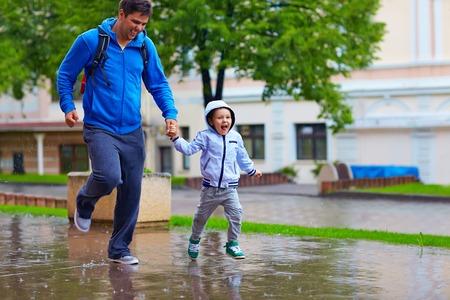 uomo sotto la pioggia: felice padre e figlio in esecuzione sotto la pioggia
