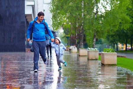 sotto la pioggia: felice padre e figlio in esecuzione sotto la pioggia