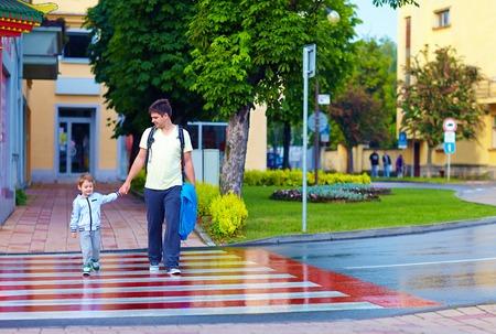 senda peatonal: padre e hijo de cruzar la calle de la ciudad en el cruce de peatones Foto de archivo