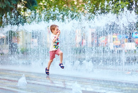 cooling: excited boy running between water flow in city park