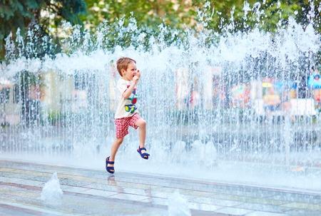 ragazzo eccitato che corre tra il flusso di acqua nel parco della città