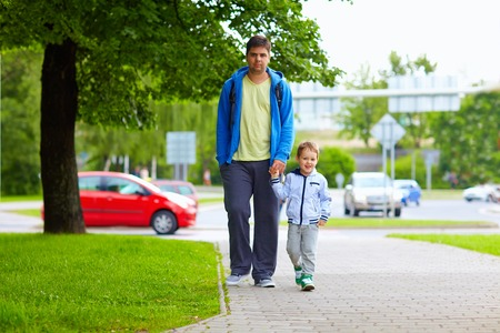 father and son walking on city street photo