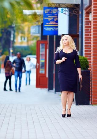 beautiful plus size woman walking the city street photo