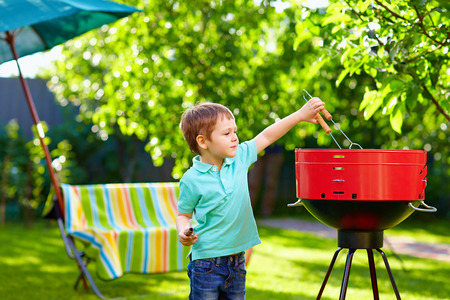 garden barbecue: kid grilling food on backyard party Stock Photo