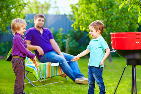 happy kids fighting with kitchen items on picnic photo