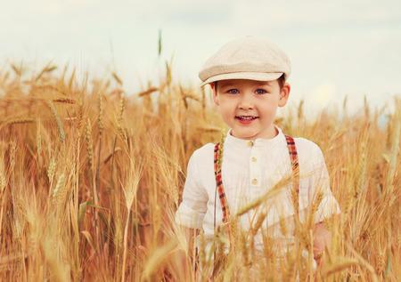 cute smiling boy walking the wheat field photo