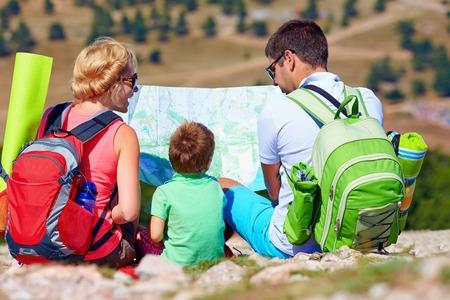 planificacion familiar: familia feliz en las montañas de discusiones sobre la ruta Foto de archivo
