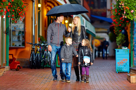 happy family walking under the rain on cozy colorful street photo