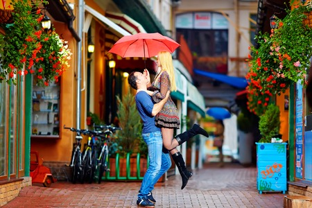 love in rain: couple in love having fun under the rain