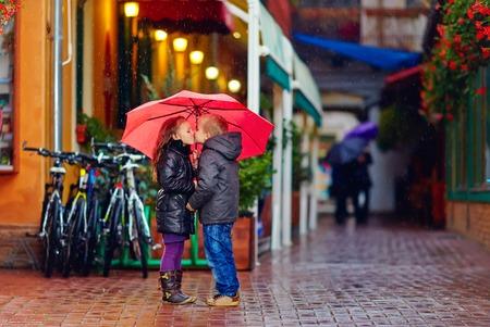 sotto la pioggia: cute giovane coppia baciarsi sotto la pioggia
