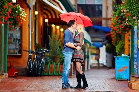 young couple kiss: pareja de enamorados bes�ndose bajo la lluvia