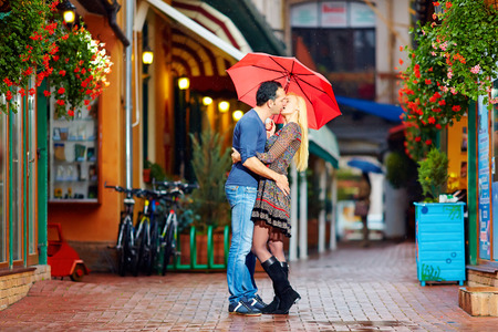 couple in rain: happy couple in love kissing on rainy street