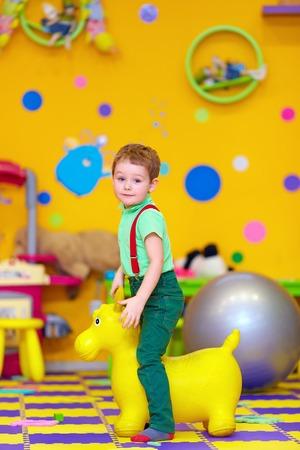 happy kid riding a toy in kindergarten photo