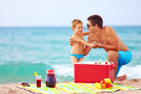 family having fun on beach picnic